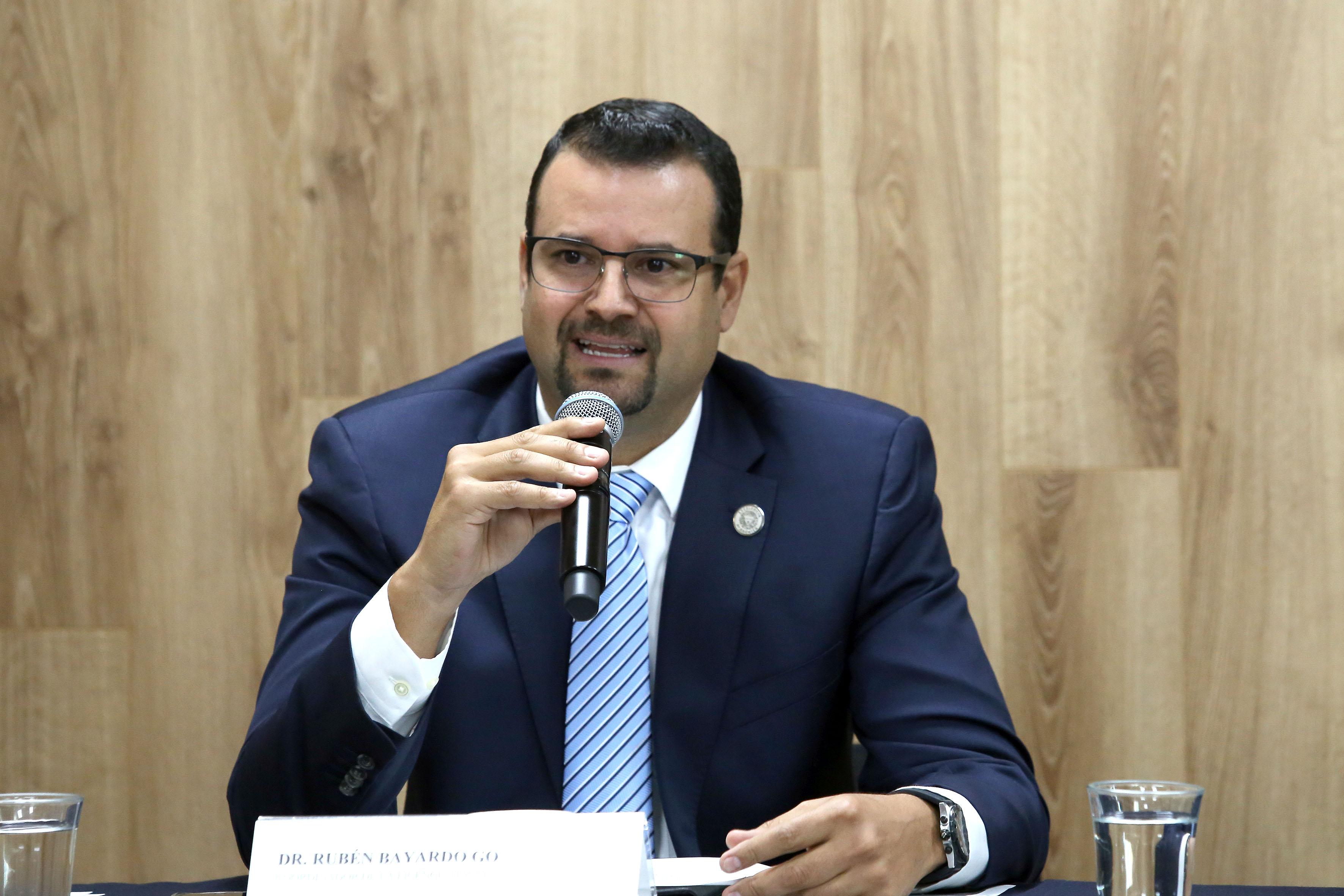 Dr. Rubén Bayardo, foto individual haciendo uso del micrófono