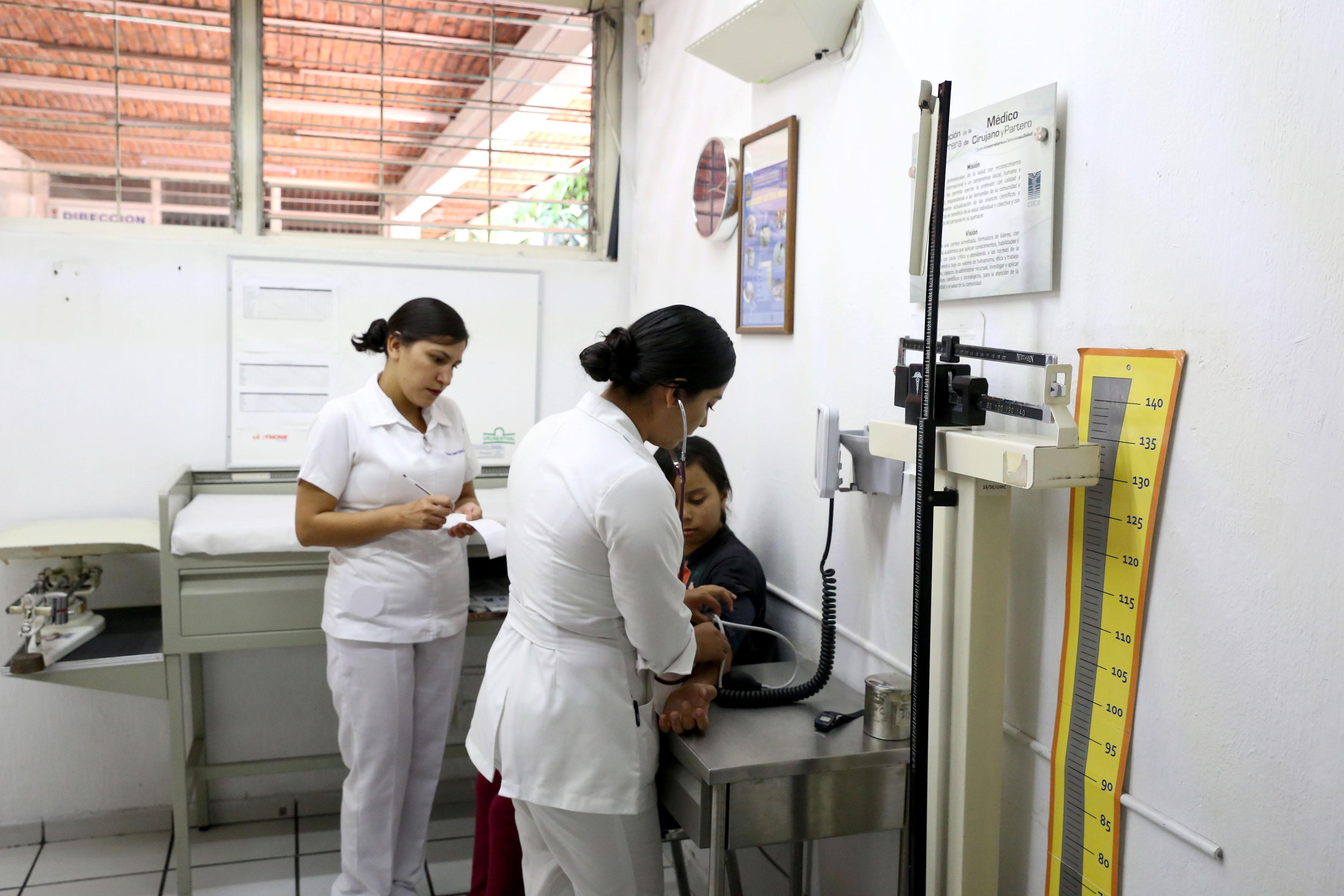 Enfermeras tomando la presión a un paciente adulto