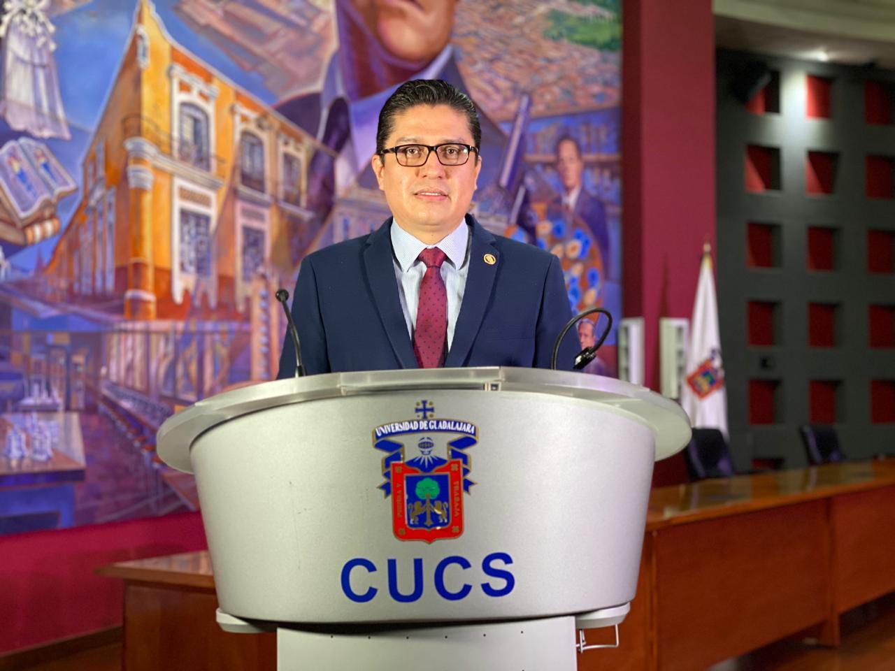 Rector CUCS, al micrófono en el pódium ofreciendo mensaje virutal de bienvenida