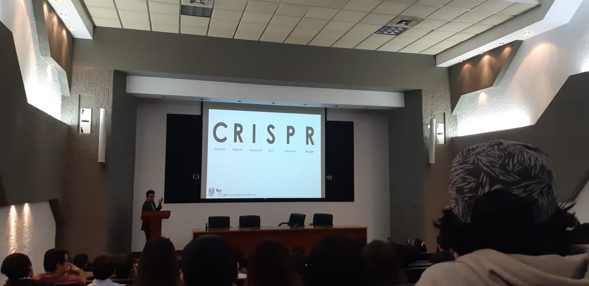 Fotografía tomada desde el fondo del auditorio, al fondo una diapositiva con el nombre de la conferencia