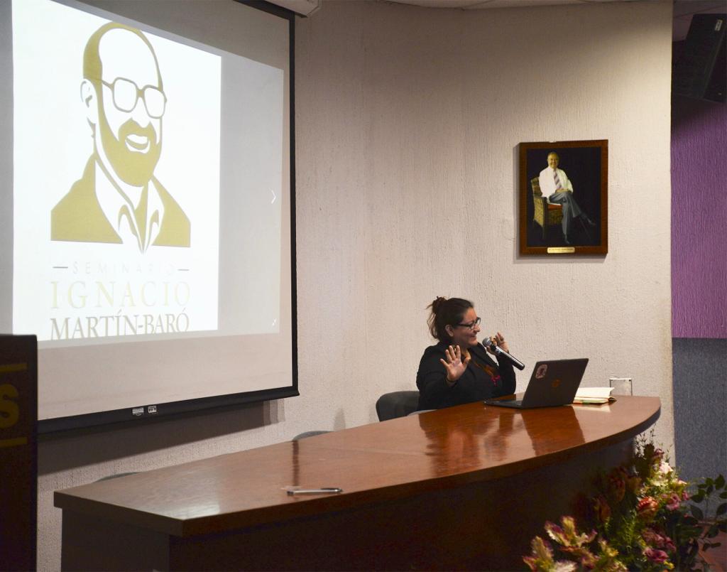 Ponente del Seminario Martín Baró dando conferencia, en la pantalla la imagen de Ignacio Martín Baró