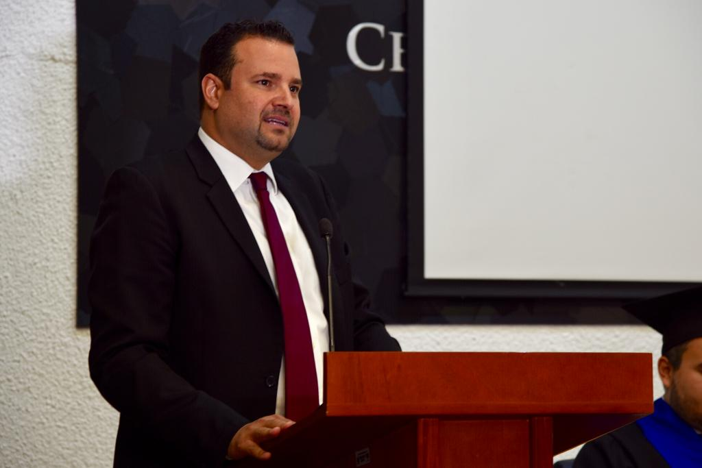 Secretario Académico en pódium dirigiendo mensaje a graduados