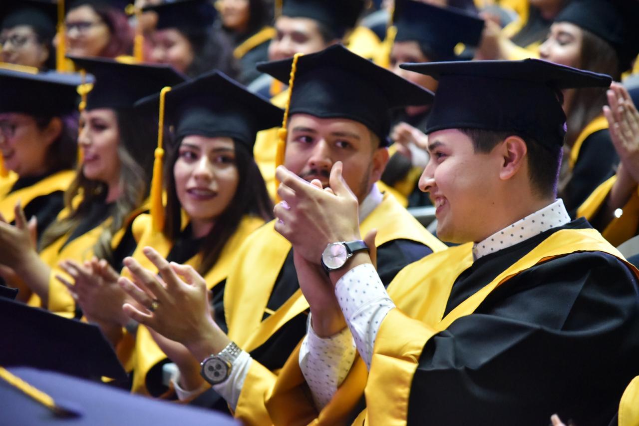 Foto cerrada de graduados luciendo toga y birrete aplaudiendo