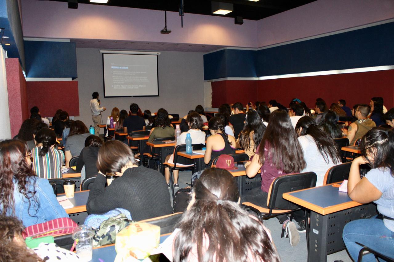 Auditorio lleno de alumnos y docentes, toma desde atras