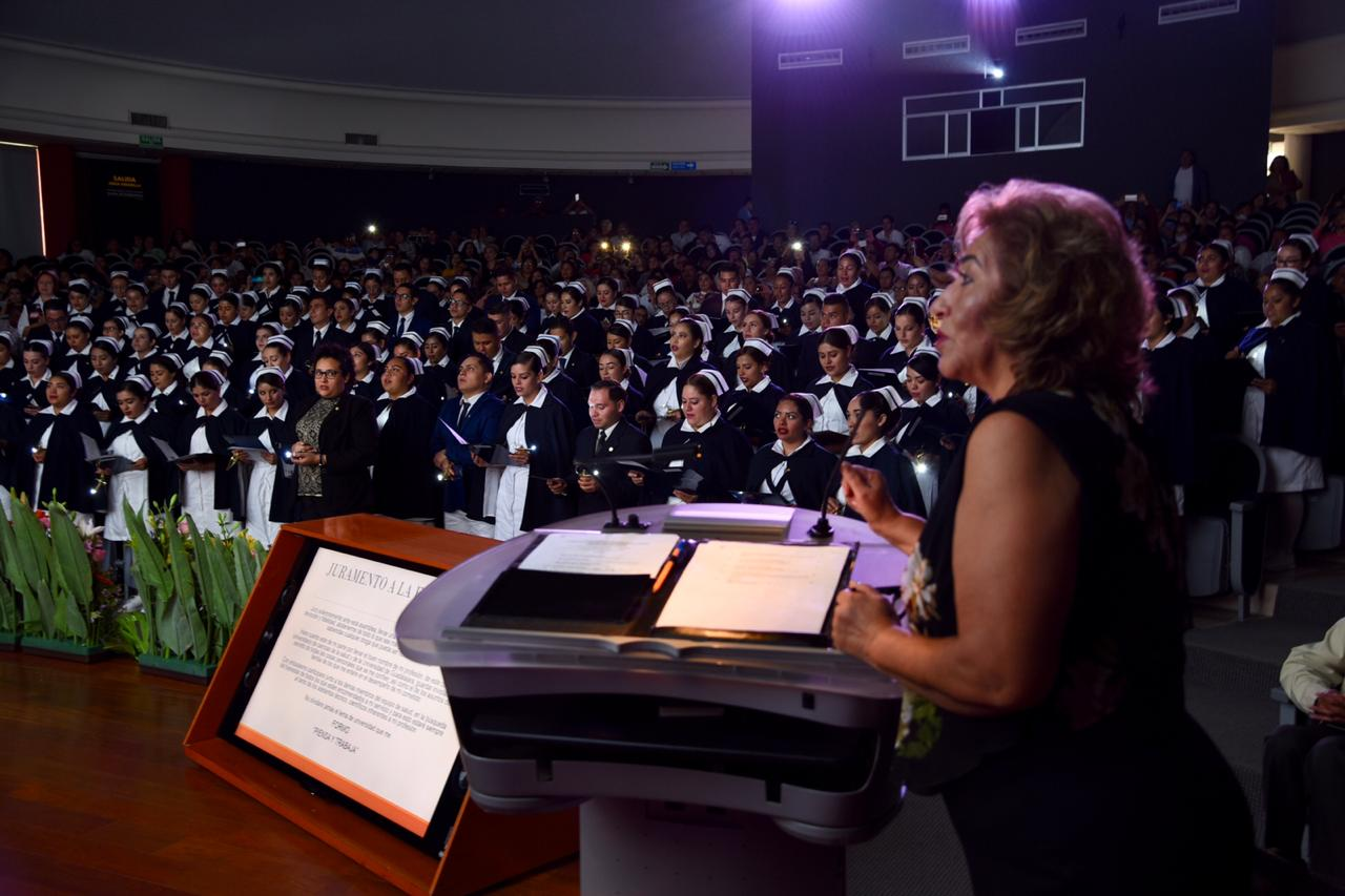 Coordinadora de carrera ofreciendo mensaje a graduados en el pódium, al fondo el auditorio lleno a toda su capacidad