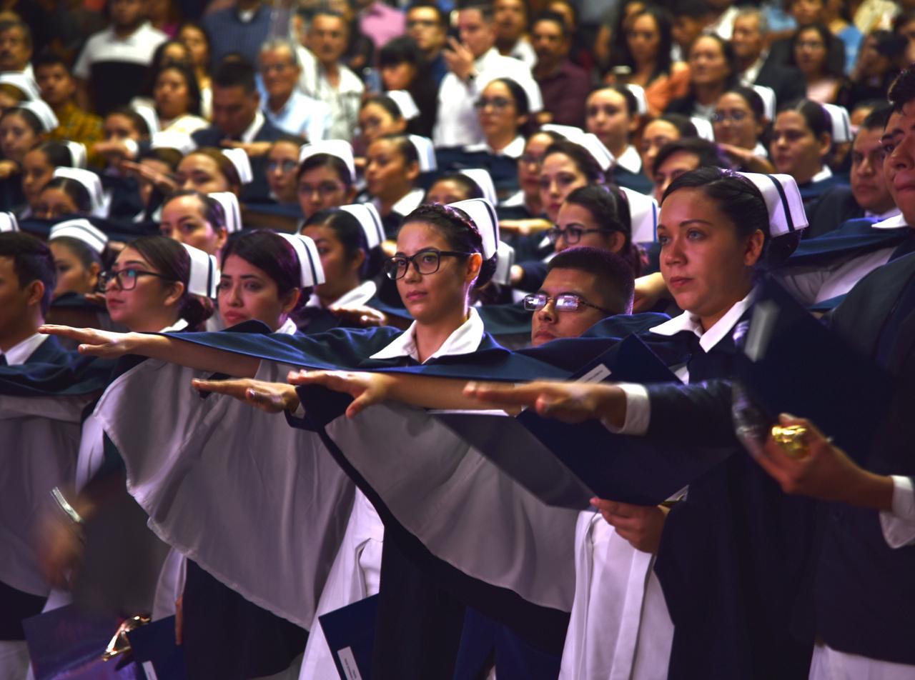 Graduadas rindiendo protesta de pie con el brazo extendido hacia el frente