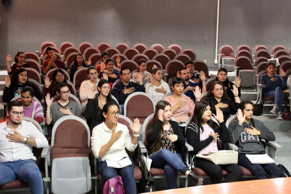 Alumnos desde sus butacas haciendo señas que les enseñó el profesor