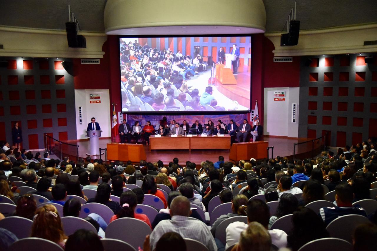 Toma general del auditorio, al fondo el rector dando mensaje en el pódium