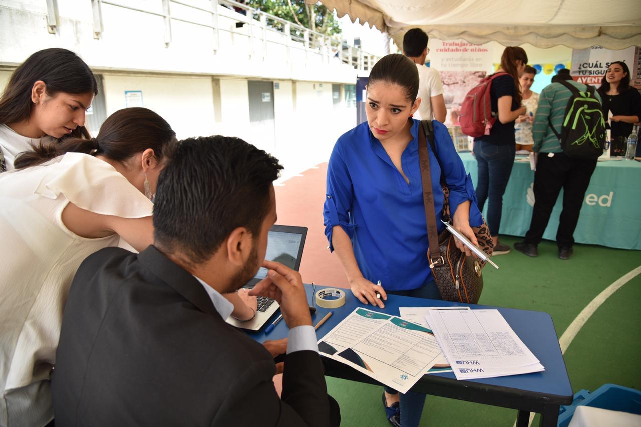Prospecta haciendo preguntas a empleadores en stand