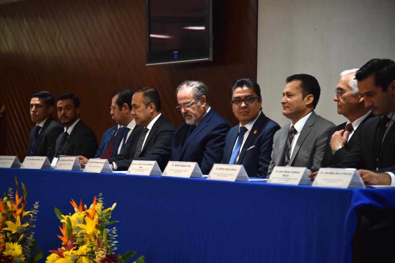 Rector del CUCS sentado al lado del secretario de salud en la mesa del presídium