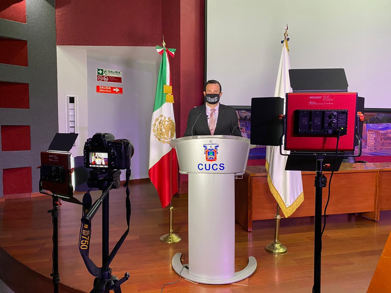Secretario Académico, al micrófono en el pódium ofreciendo mensaje virtual de bienvenidia