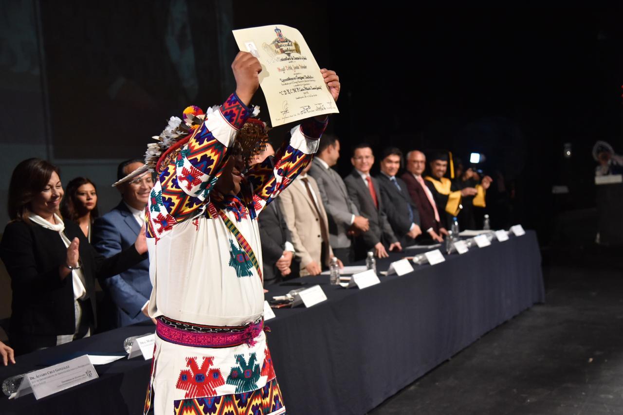 Egresado Wixárica levantando su reconocimiento en el escenario del teatro