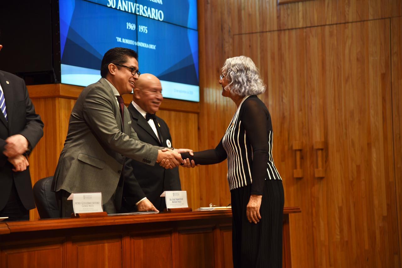 Dr. Muñoz entregando reconocimiento a egresada de la generación
