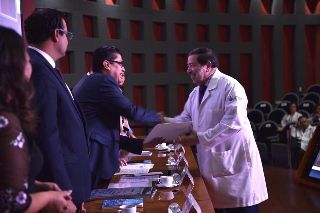Rector entregando reconocimiento a médico