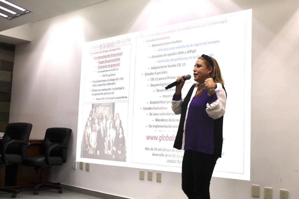 Ponente impartiendo conferencia, diapositiva en la pantalla