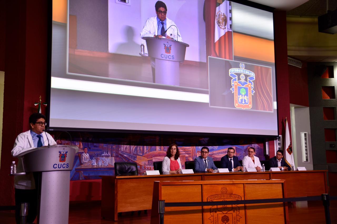 Coordinador de Investigación del IMSS al micrófono en el pódium, al fondo los miembros del presídium y en la pantalla su imagen