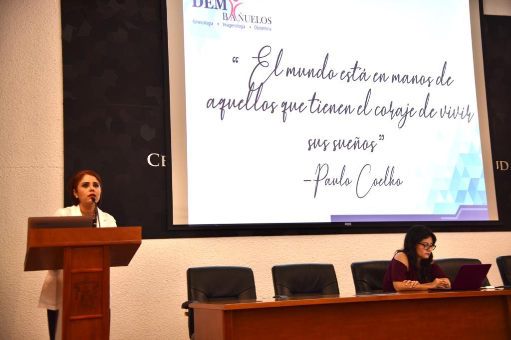 Conferencista en el pódium, al fondo una diapositva con una frase de Pablo Cohelo
