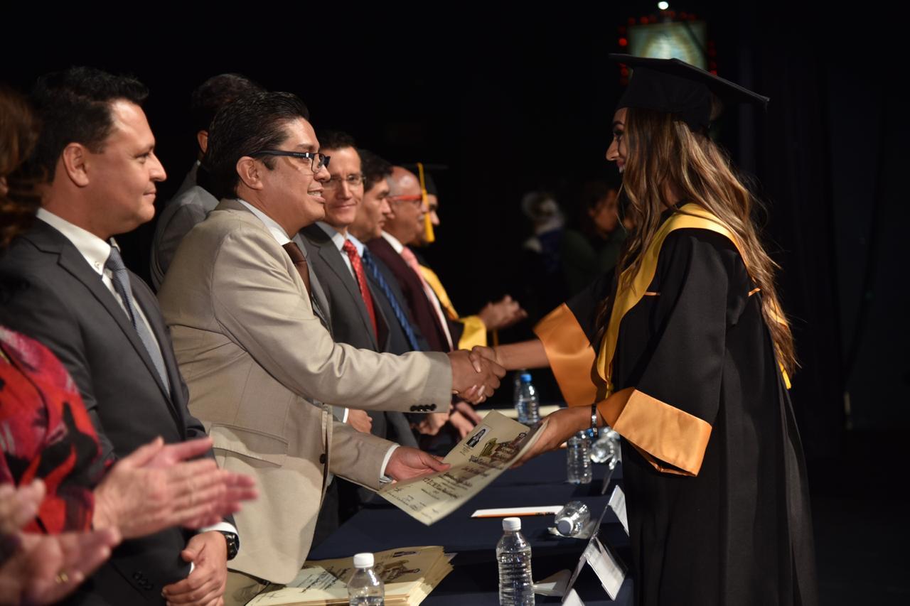 Rector entregando reconocimiento a graduada