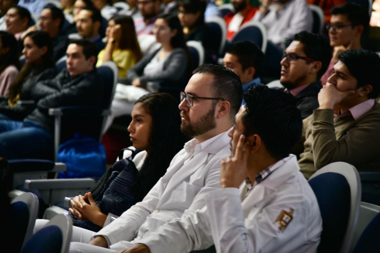 Médicos residentes en bata blanca escuchando a los ponentes