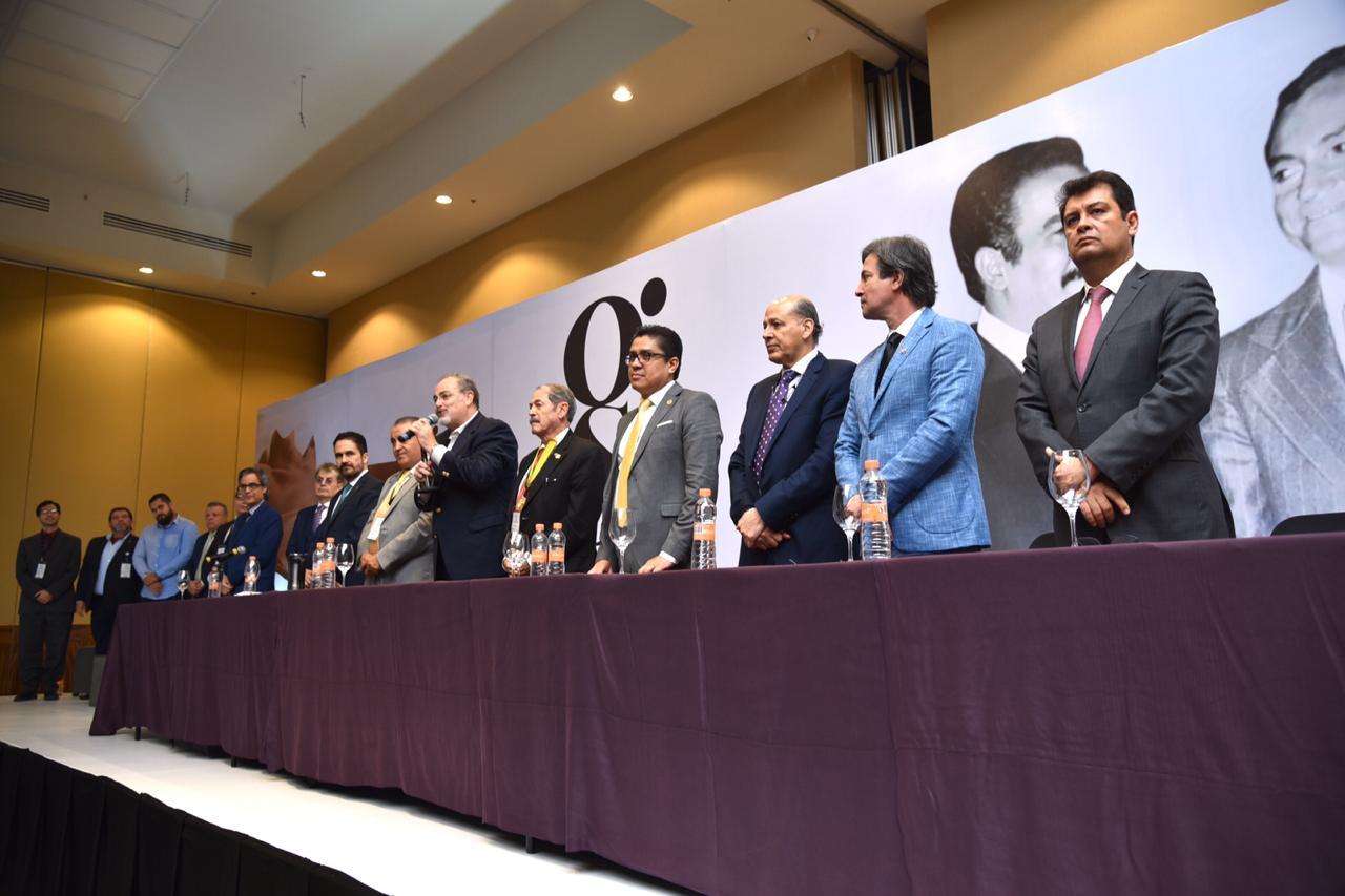 Membros del presídium de pie durante el acto inaugural
