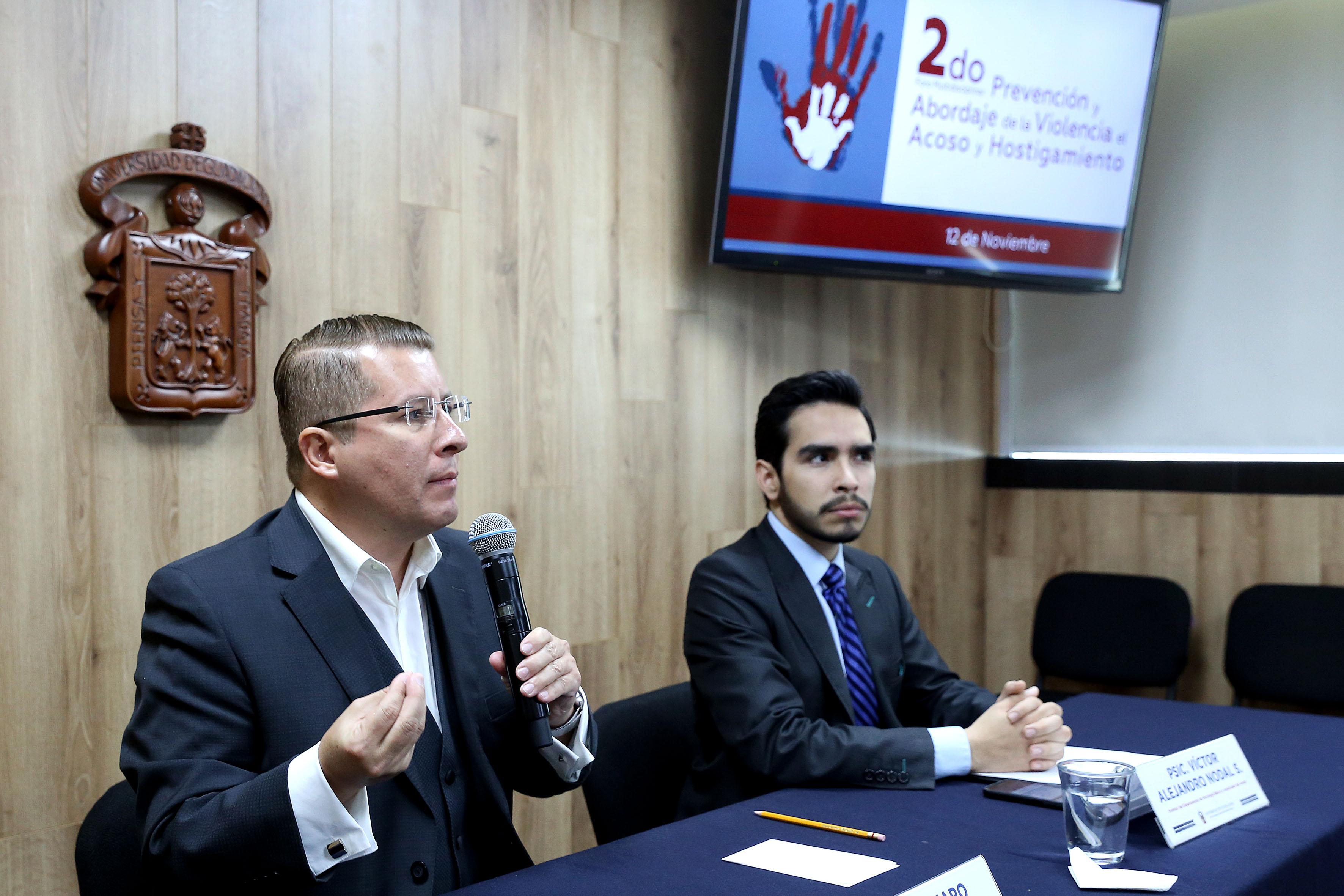 Dr. Dante Haro al micrófono en Rueda de Prensa, a su lado académico del CUCS