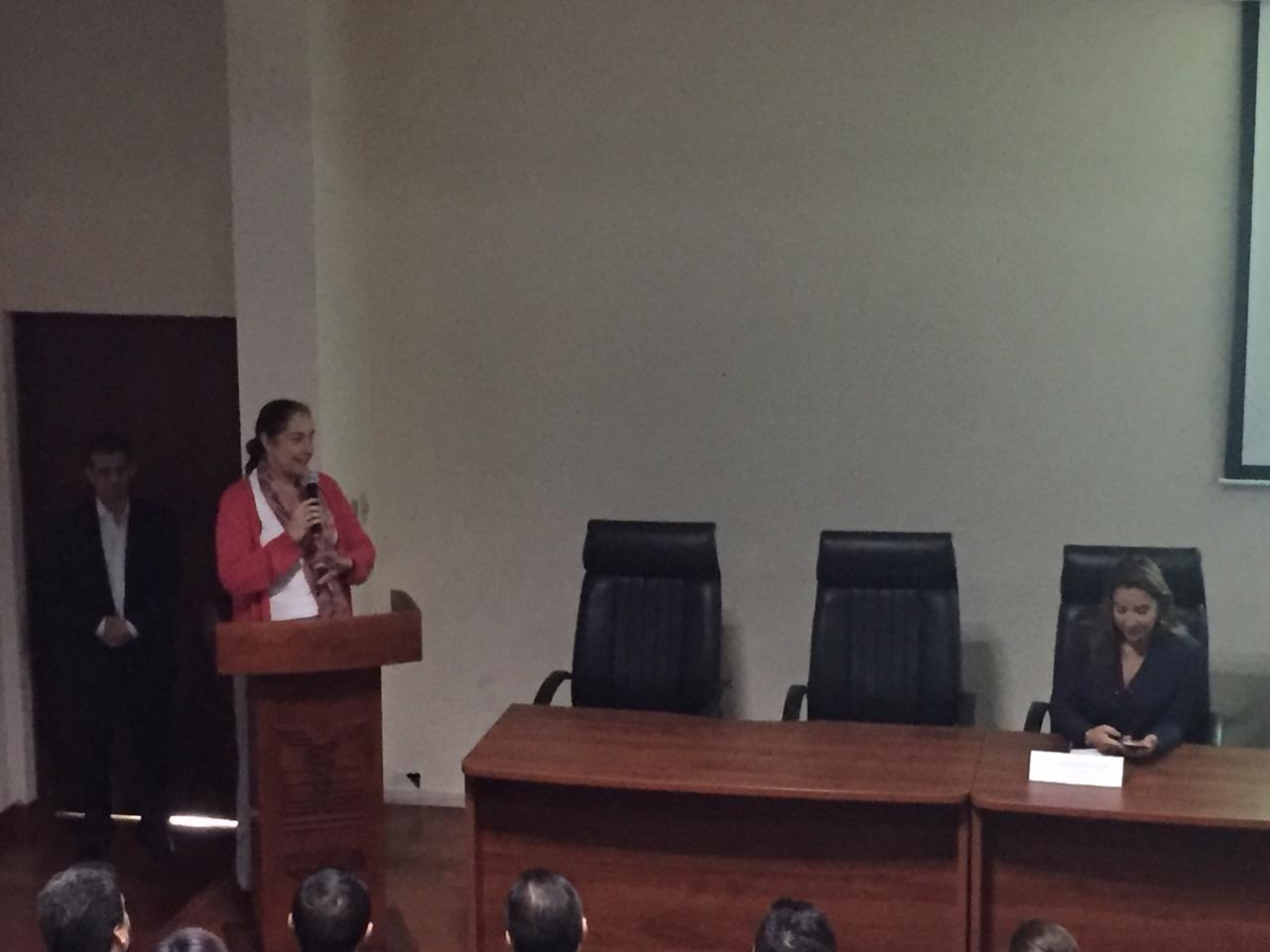 Dra. Bárbara Vizmanos al micrófono en el podio
