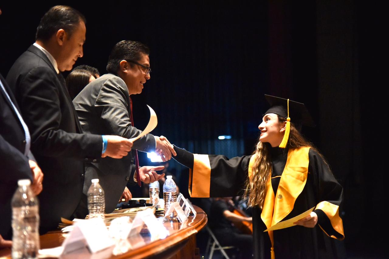 Rector del CUCS saludando a alumna graduada al entregarle su pergamino
