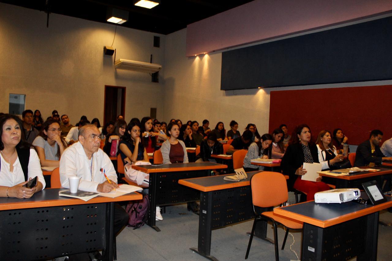 Auditorio lleno de alumno y docentes, toma de frente