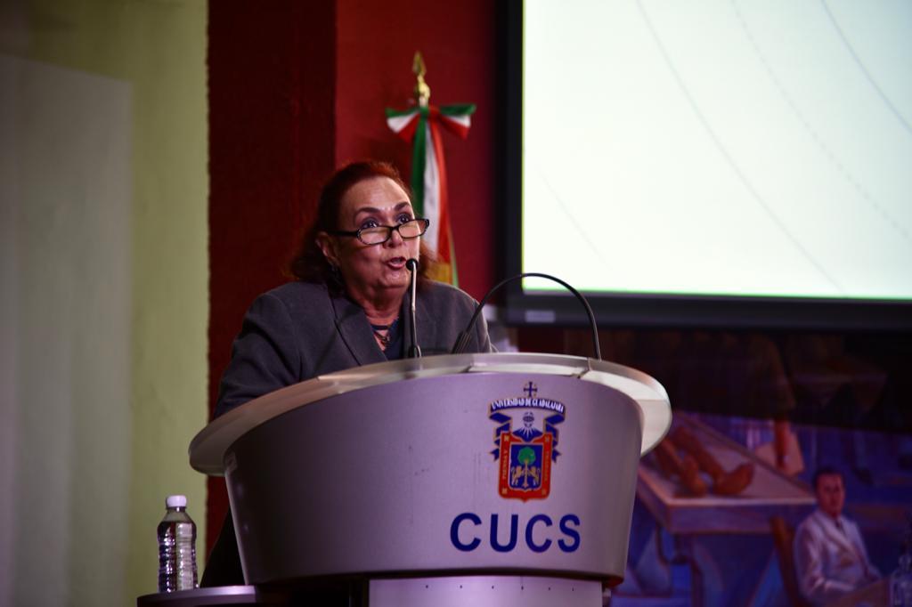Coordinadora de Servicios Académicos al micrófono en el pódium