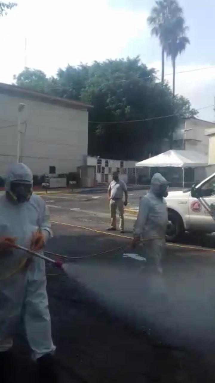 Personal de Protección Civil sanitiazando el estacionamiento de la puerta 13 del CUCS