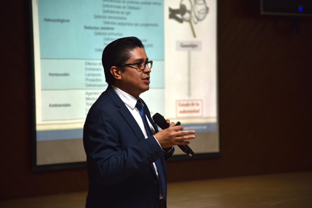 Rector del CUCS impartiendo conferencia, atrás una diapositiva