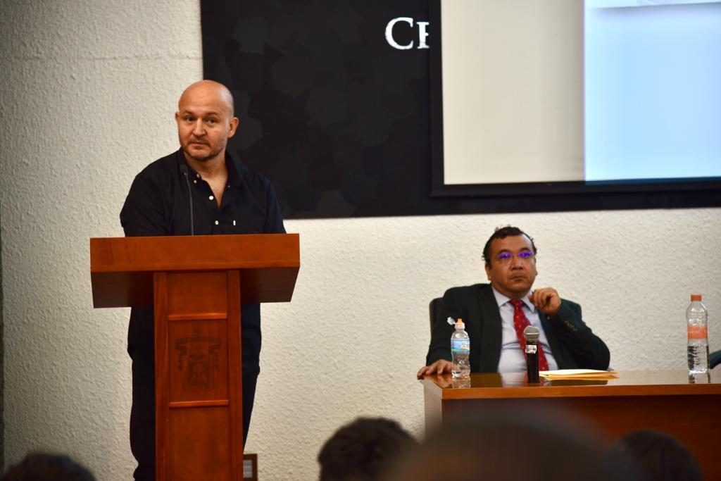 Ponente impartiendo conferencia, al fondo del coordinador de la carrera de TSU en Terapia Respiratoria