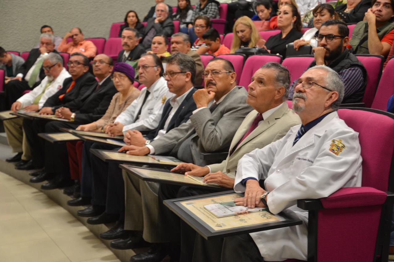 Médicos homenajeados escuchando discursos con su reconocimiento