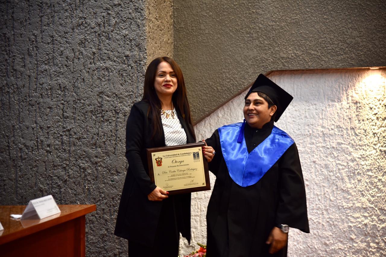 Madrina de generación y representante de los graduados posan para la foto