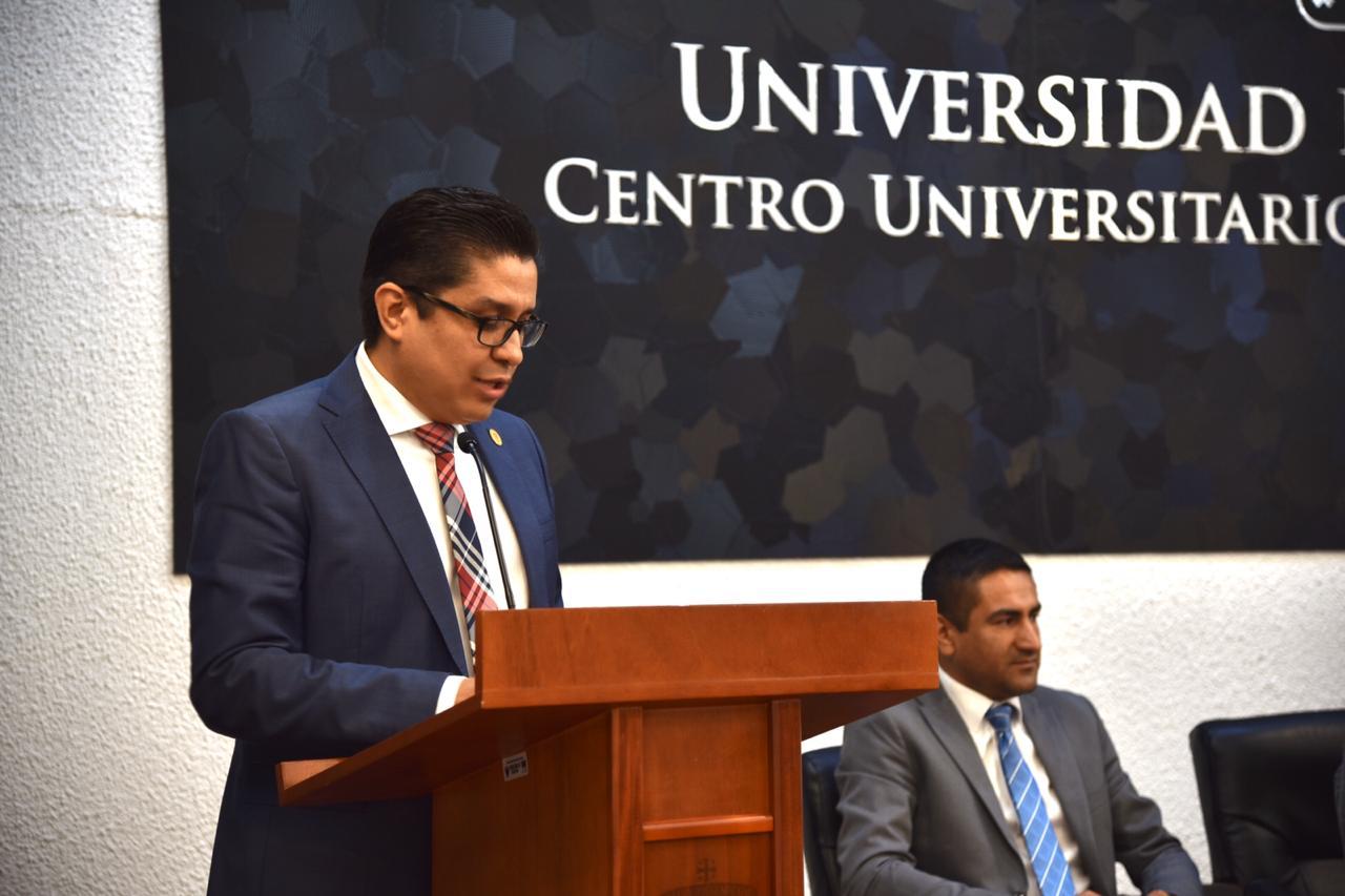 Rector del CUCS al micrófono en el pódium declarando inaugurado evento