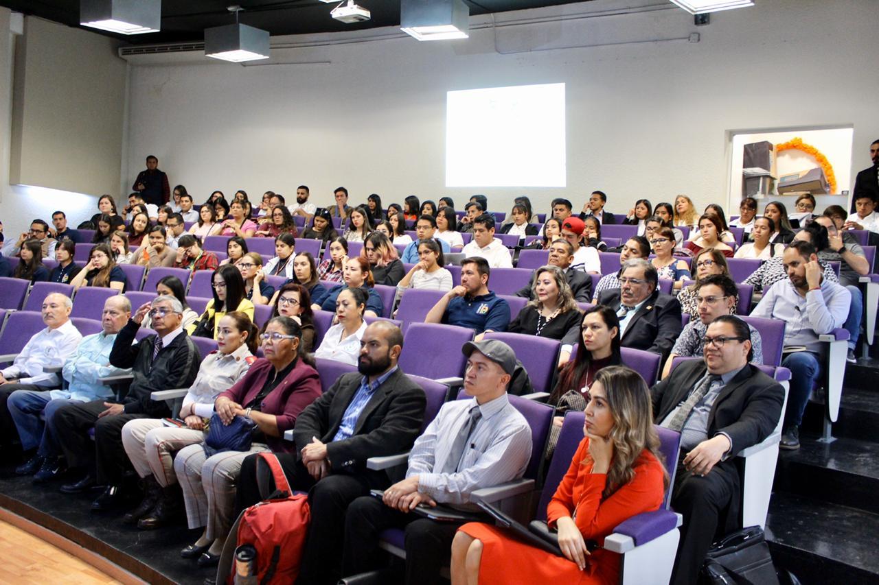 Asistentes sentados atentos a la conferencia, foto general donde se visualiza el auditorio a lleno total