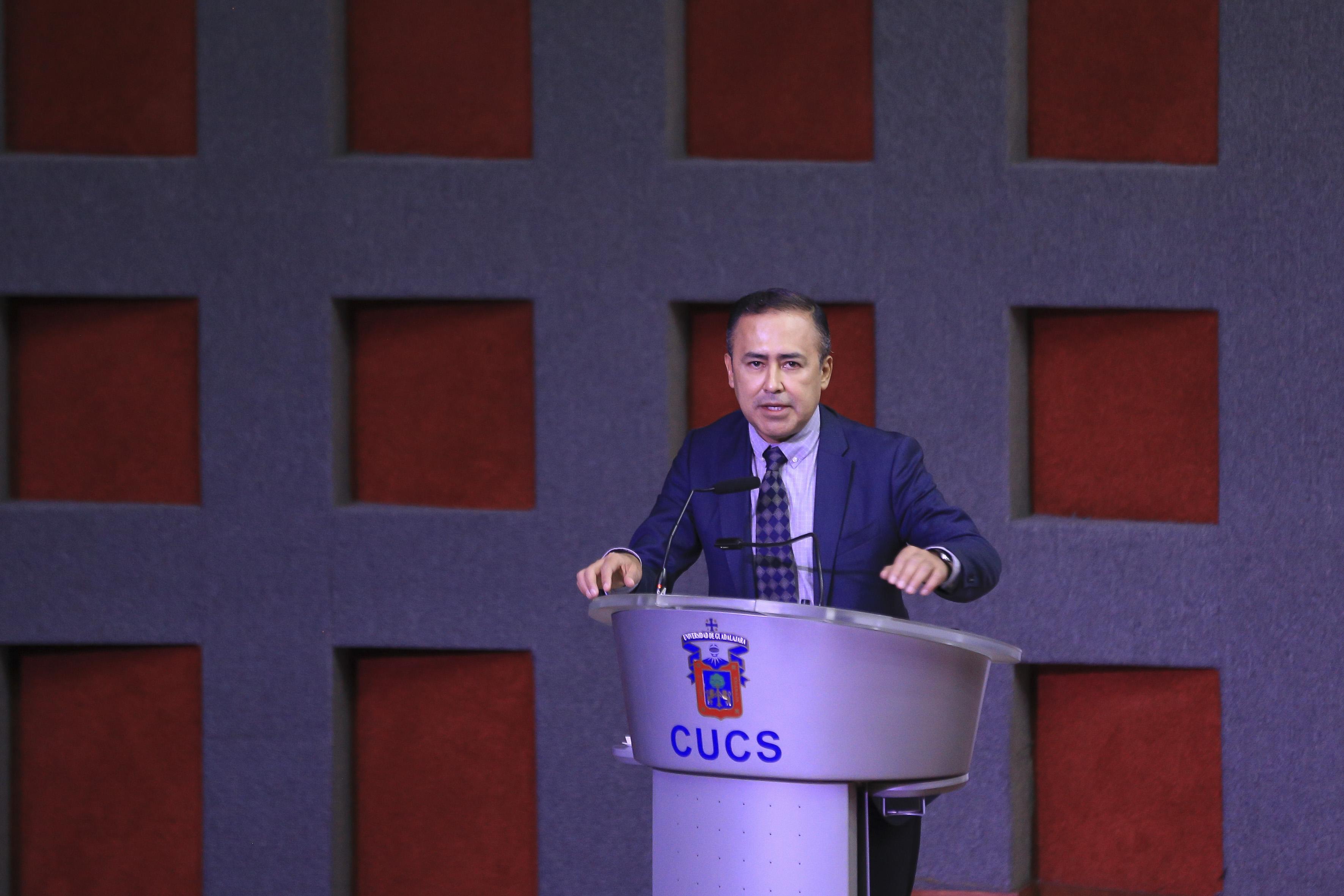 Rector CUCS en el podio ofreciendo mensaje
