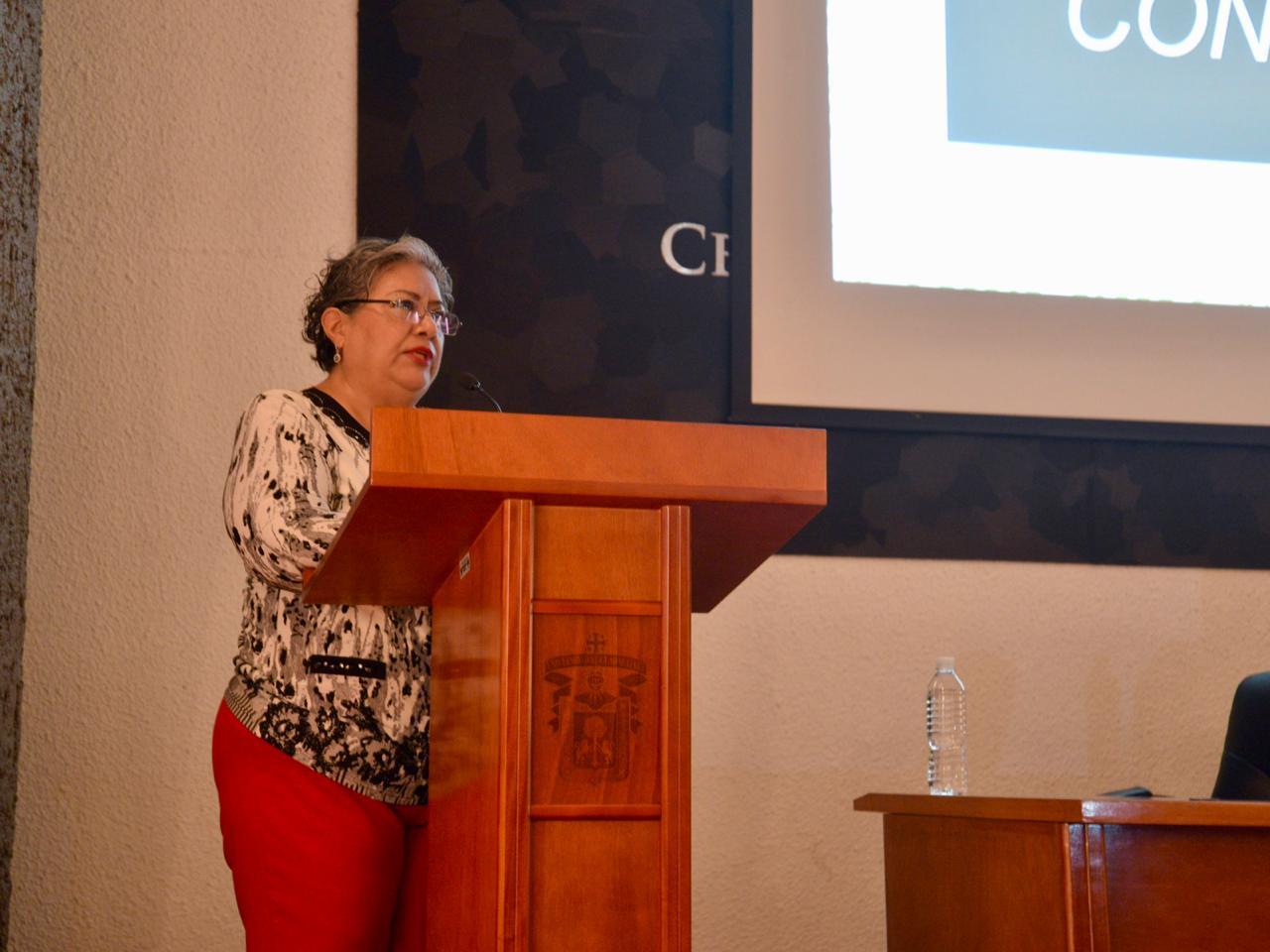 Dra. Getzabel Gallardo impartiendo conferencia en el podio