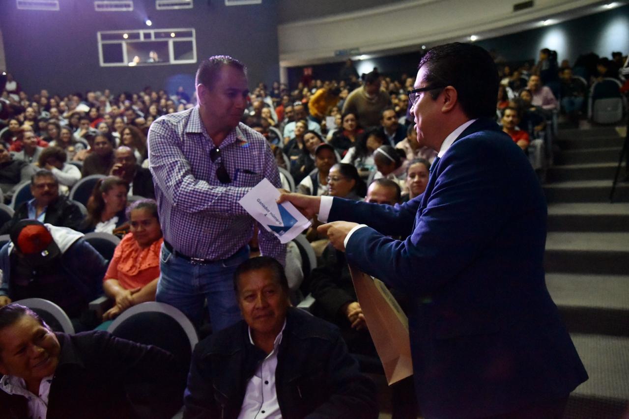 rector del cucs entregando paquete de libros a padres de familia en su butaca