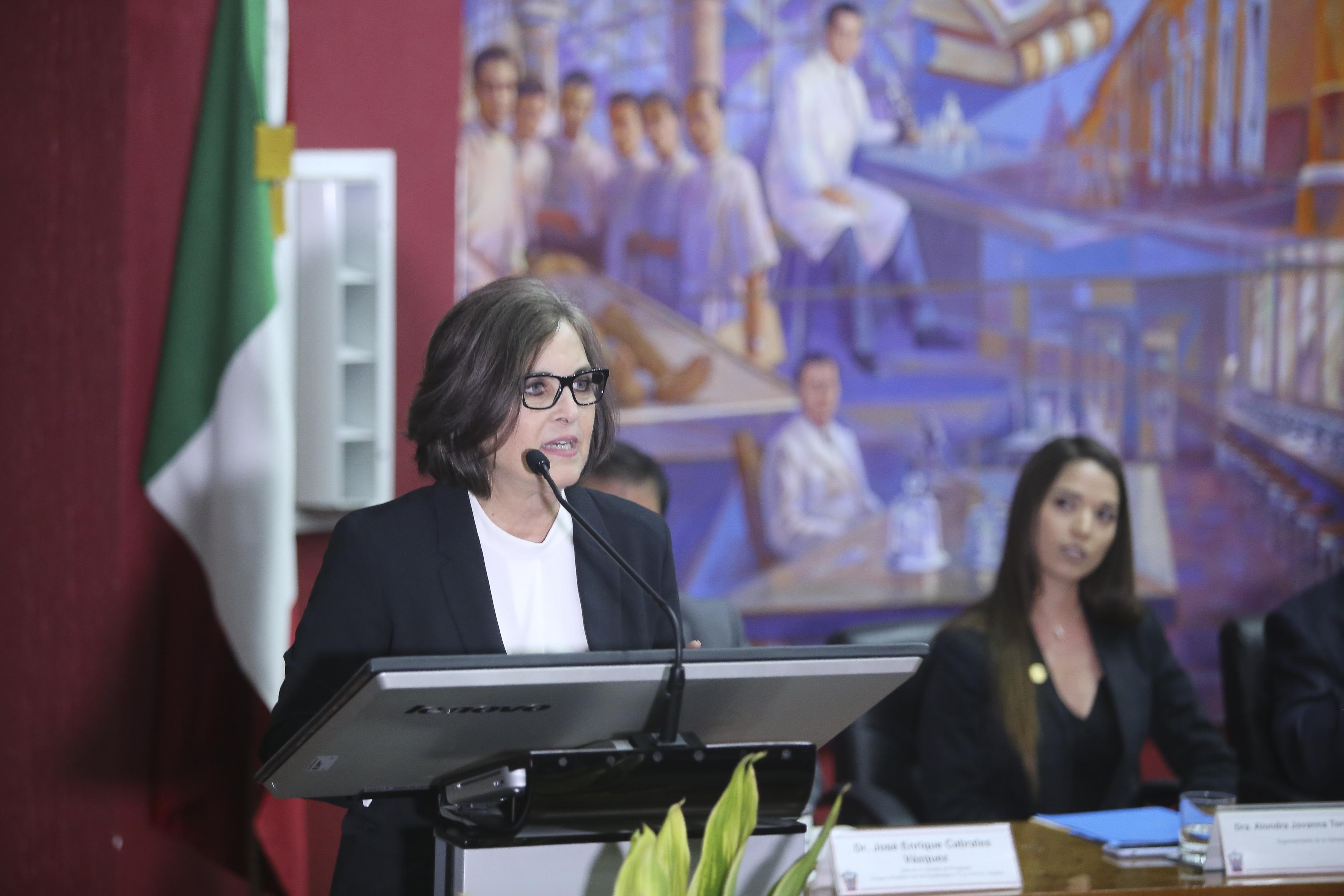 Madrina de la generación al micrófono en el podium