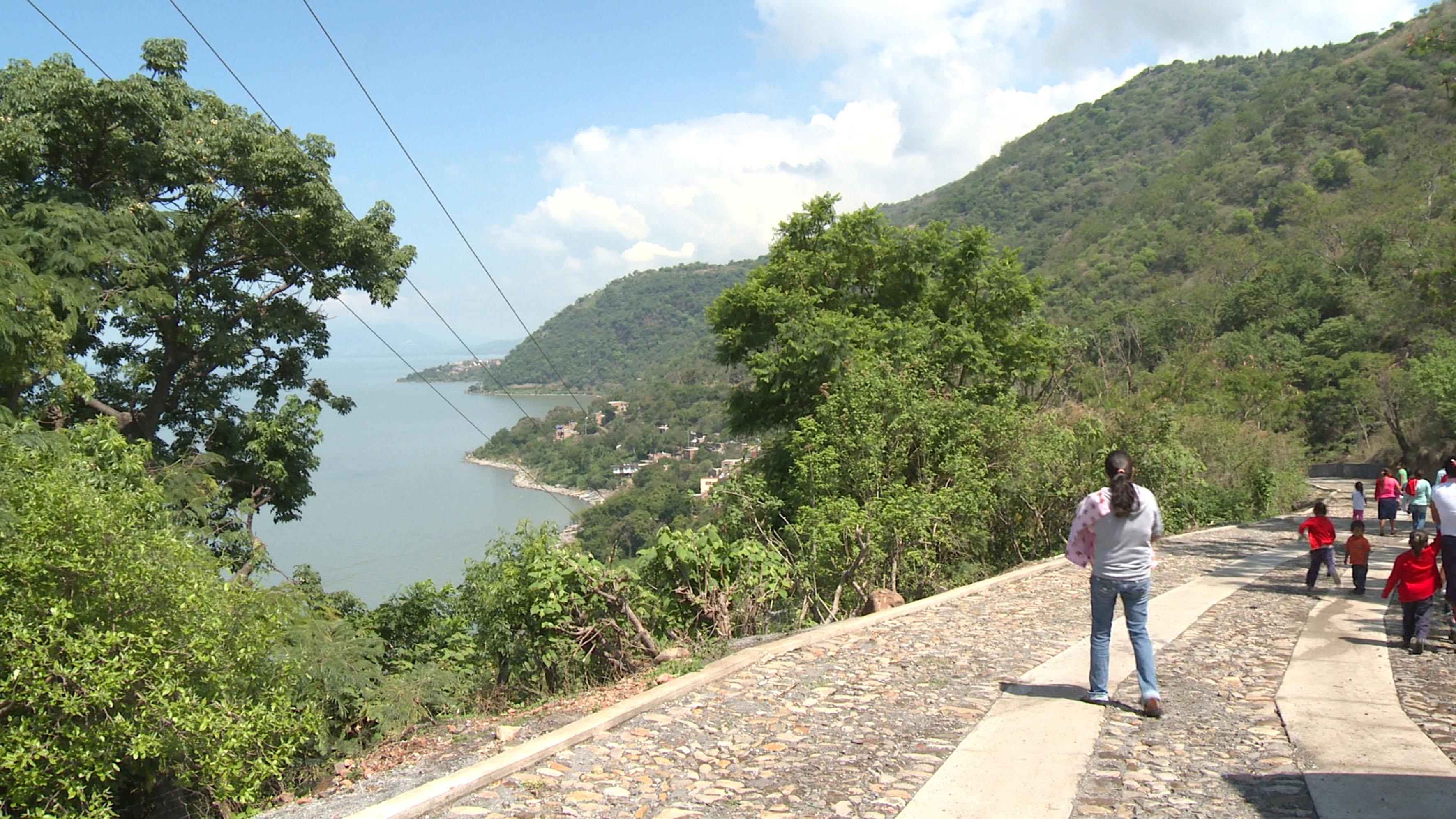 camino de Agua Caliente, niños transitando a pie y una señora cargando a su bebé