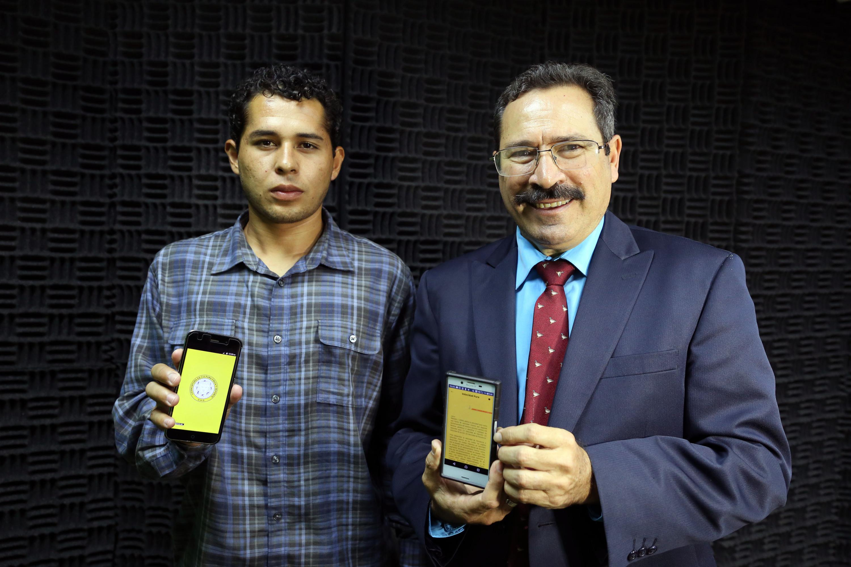 Maestro y alumno muestran la aplicación en sus teléfonos celulares