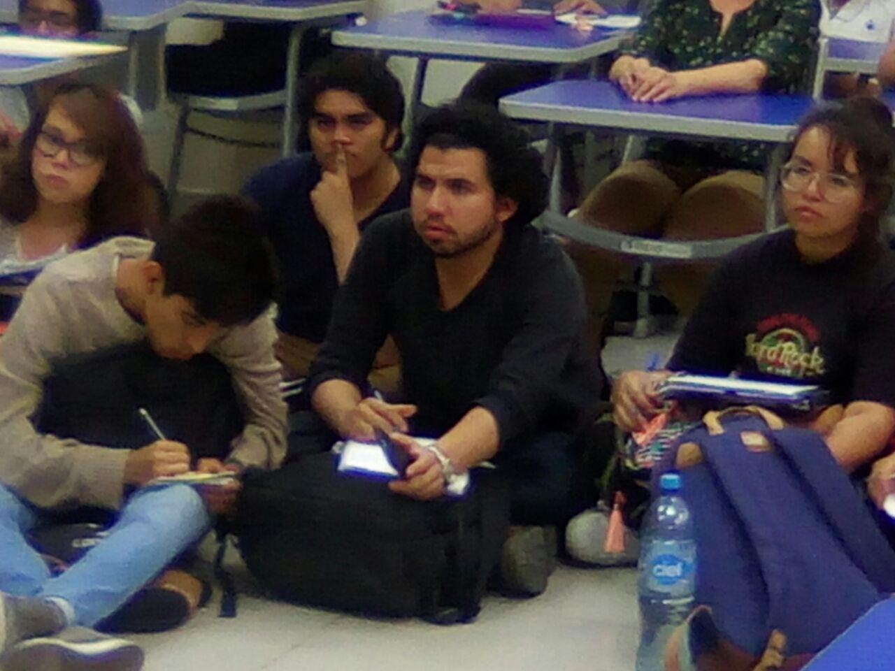 Alumnos sentados en el suelo durante el conversatorio