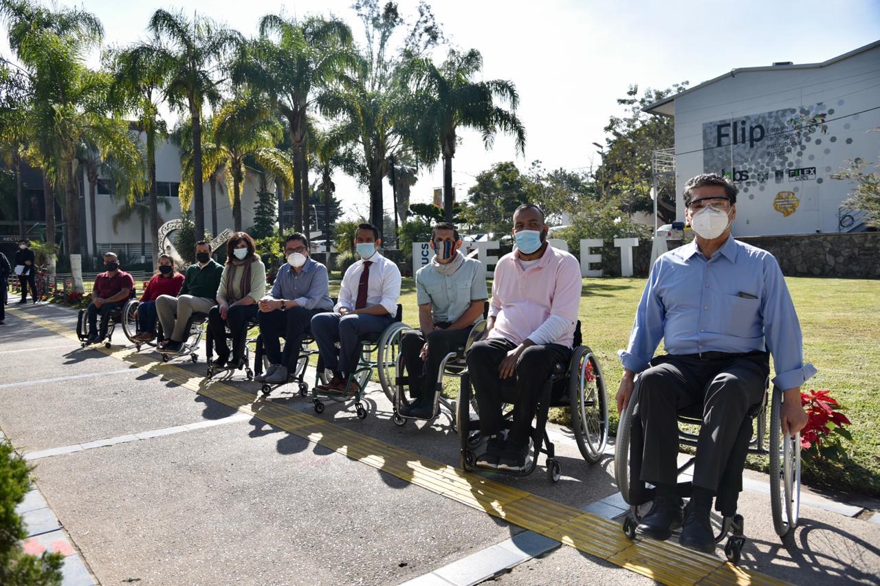 Funcionarios y directivos sentados en silla de ruedas posando para la foto