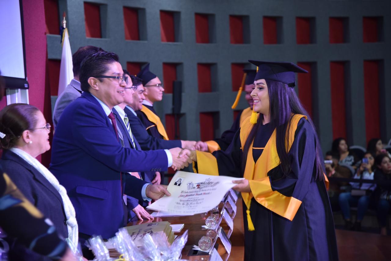 Rector entregando constancia a graduada