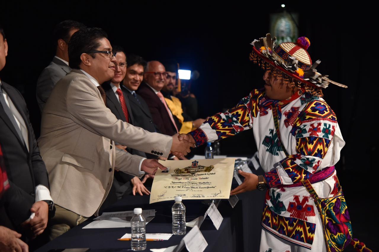 Rector entregando reconocimiento a graduado wixárica