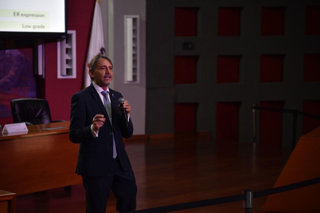 Ponente impartiendo conferencia abajo del escenario