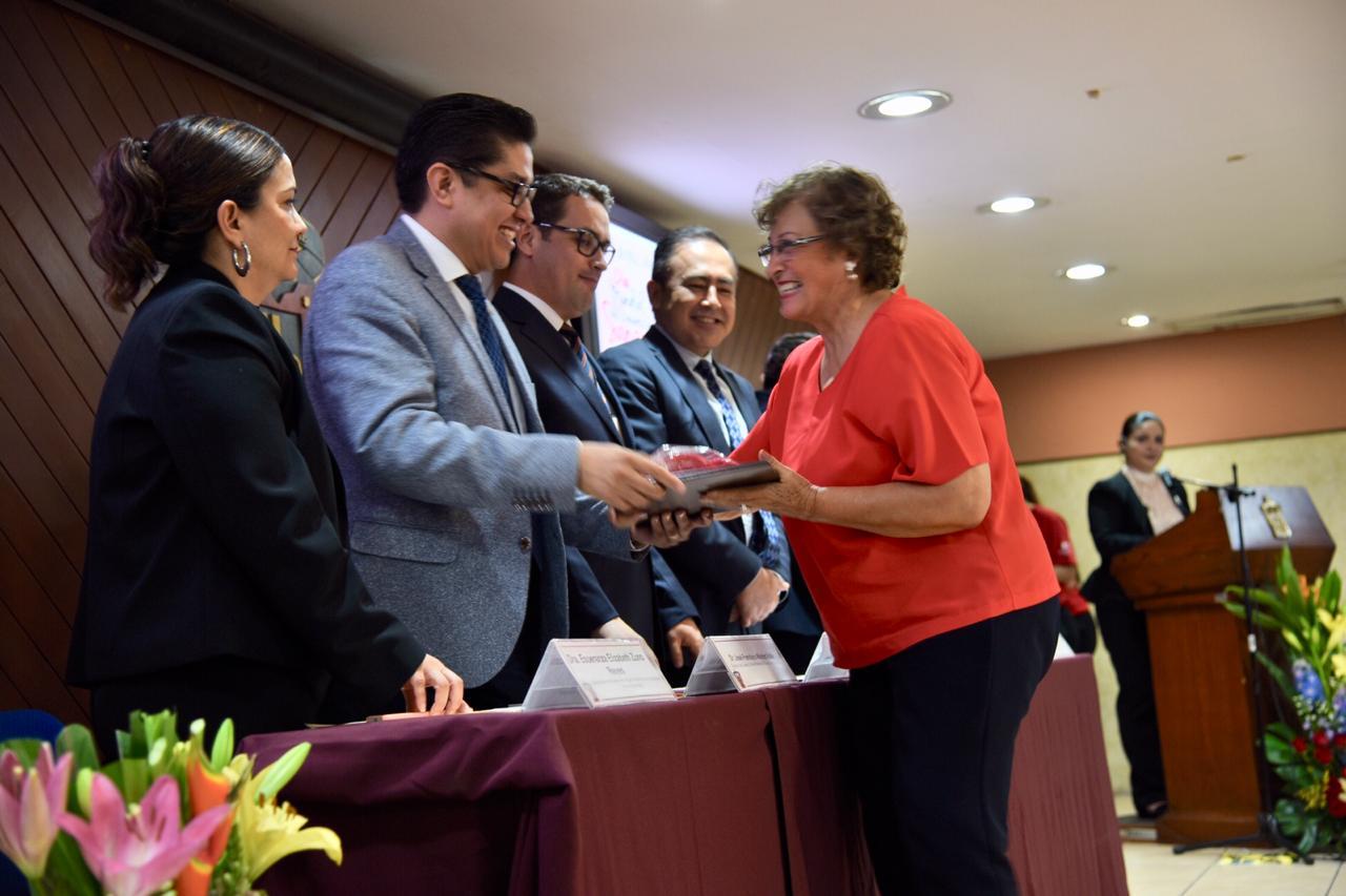 Dra. Cuquita recibiendo reconocimiento de manos del rector del CUCS