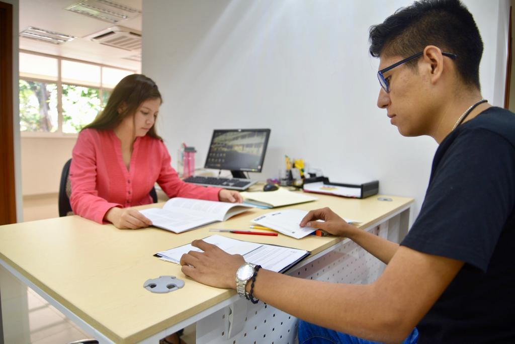 Alumnos del CUCS revisando documentos en un escritorio