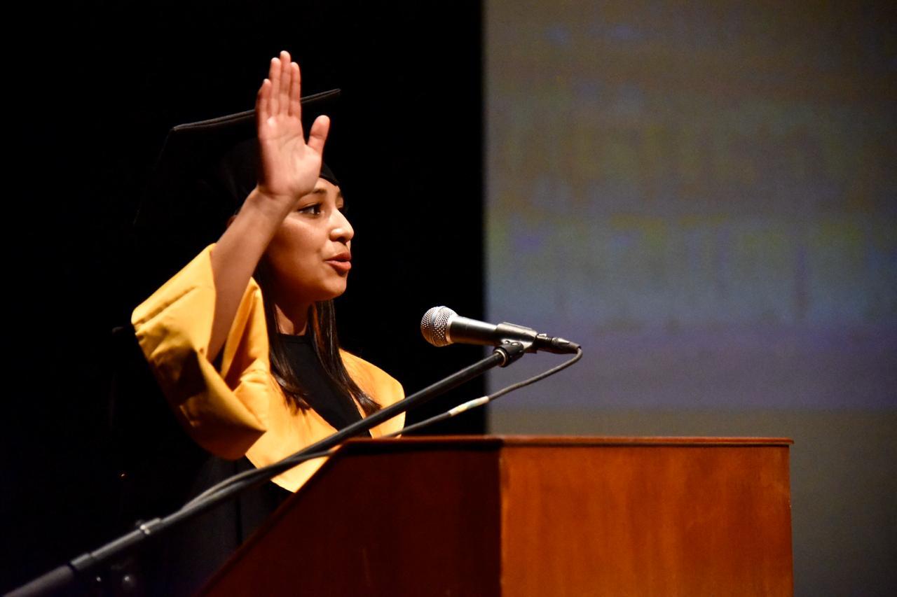 Alumna dirigiendo desde el podium el juramento hipocrático con la mano levantada